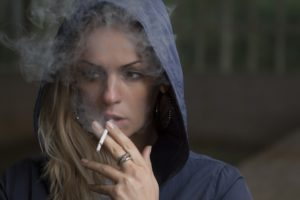 Woman smoking a cigarette wearing a hood