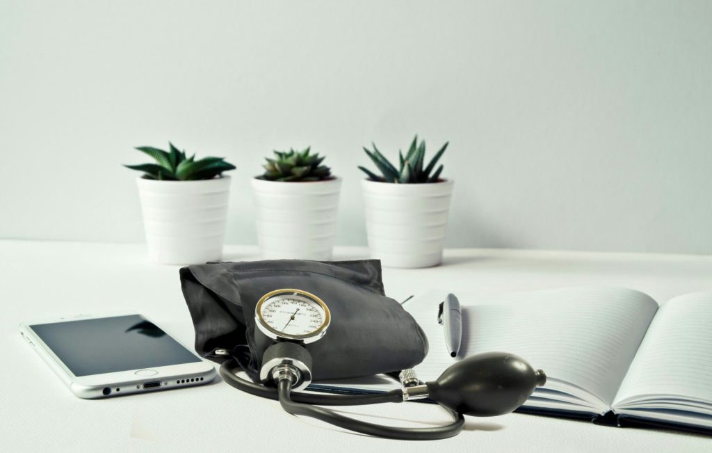 photo of an iphone, a stethoscope, and an open pad with a pen with three small plants in the background
