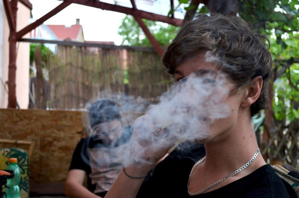young person smoking marijuana with cloud of smoke in front of their face